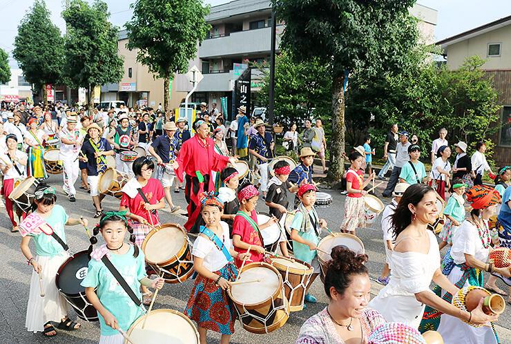 にぎやかな演奏で盛り上げるマラカトゥのグループ=福野地域中心部