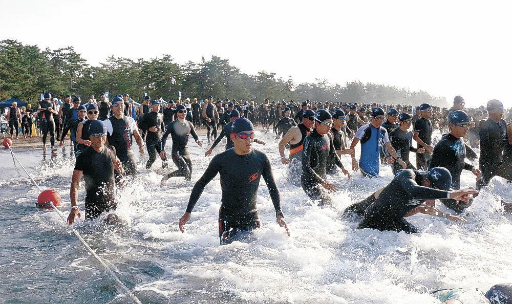 スイムで一斉にスタートするAタイプの選手=珠洲市鉢ケ崎海水浴場
