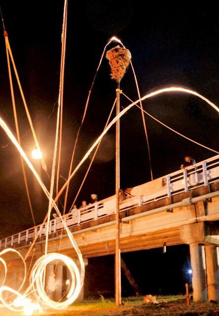 モジめがけて投げ上げられたジンが赤い放物線を描く=8月24日夜、福井県小浜市下田