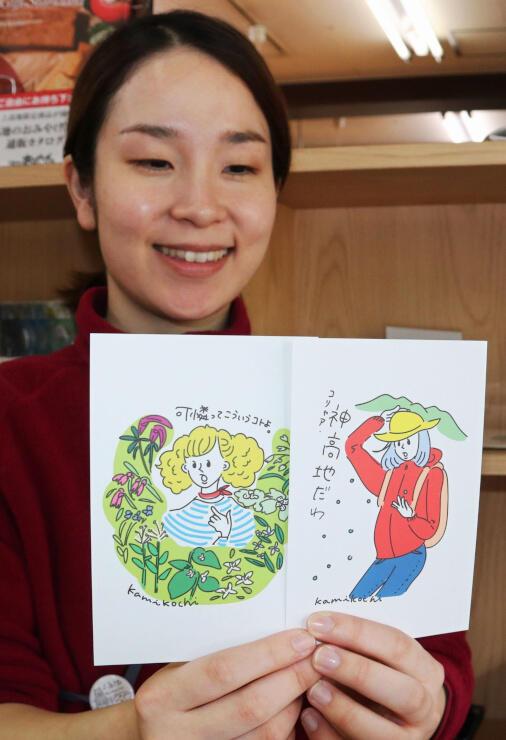 上高地を訪れる若い女性をモチーフにしたポストカードを手にする内堀さん