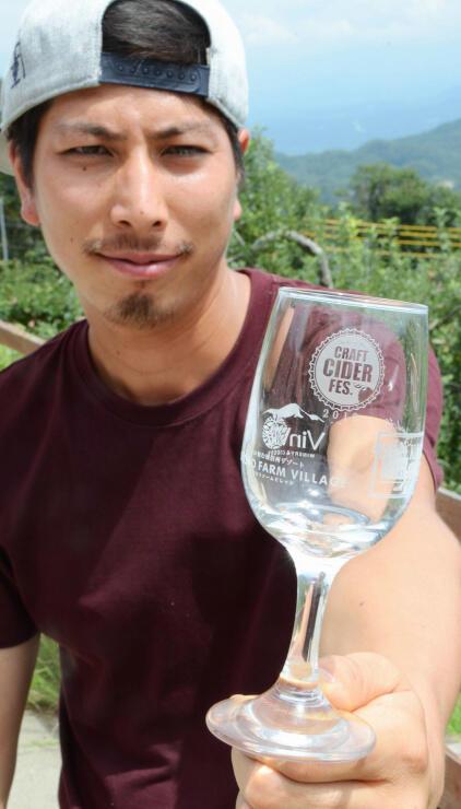 参加者に配る限定グラスを手に催しをPRする桜井さん
