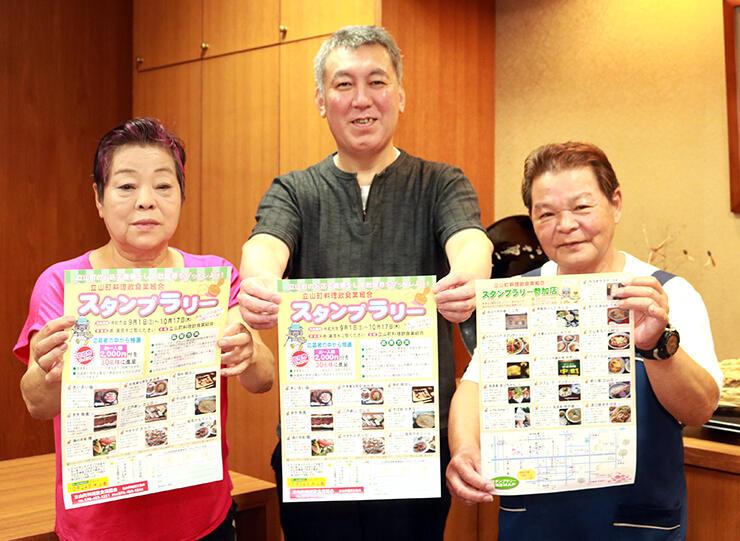 スタンプラリーのちらしを持ちPRする(左から)寺林副組合長、柴田組合長、三上副組合長
