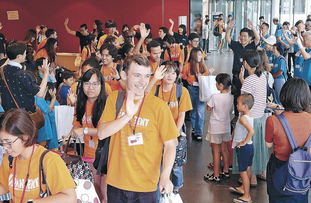 見送りのホスト家族やボランティアに手を振る留学生=北國新聞赤羽ホール