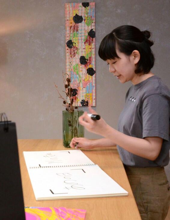 BEB5の2階に飾られた門田さんの絵画(中央奥)。絵画の前でスケッチブックに題名を書き、写真撮影してもらう