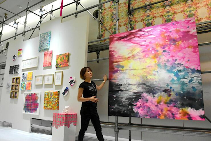 「10月のひとひら桜」(手前右)など新作が並ぶ会場に立つ越さん