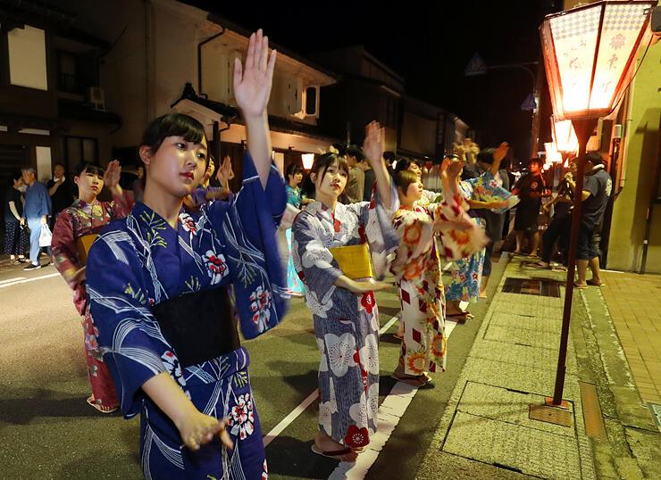 ぼんぼりが灯りおわらの準備が整った町で稽古の仕上げをする踊り手=富山市八尾町東町