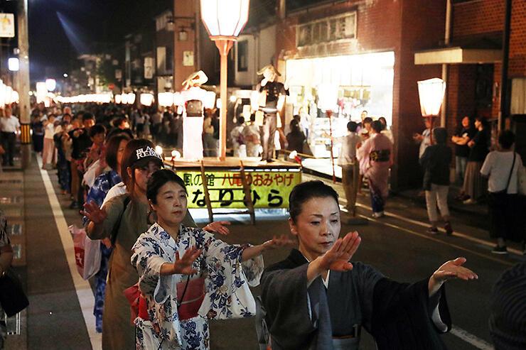 踊り手の所作に合わせ、通り一帯で「大輪踊り」を披露する観光客ら=富山市八尾町上新町