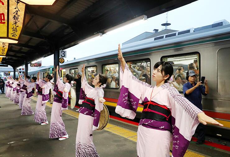 始発列車の乗客に見送りおわらを披露する踊り手たち=JR越中八尾駅