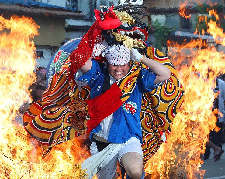 燃え盛る炎の中を駆け抜ける獅子=二口熊野社
