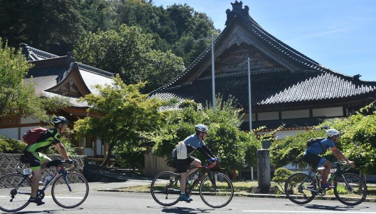 豊丘村の泉龍院の前を自転車で走る参加者