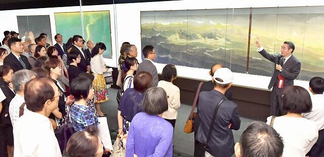 展示作品について説明をする手塚雄二さん(右奥)=9月6日、福井県福井市の福井県立美術館