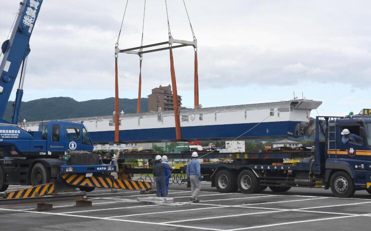 トレーラーで運んだ重さ約4トンの遊覧船前方部分をクレーンで降ろす作業=9日午前8時19分、諏訪市