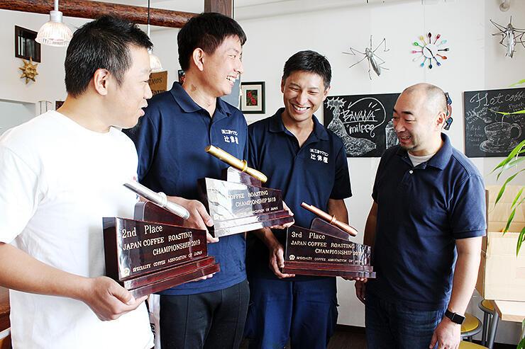 富川さん(右)に完成したトロフィーを見せる(左から)荒木さん、亮さん、悟さん