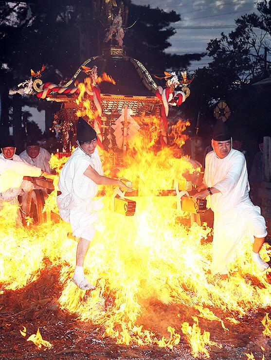 炎の中を駆け抜ける神輿=櫛田神社