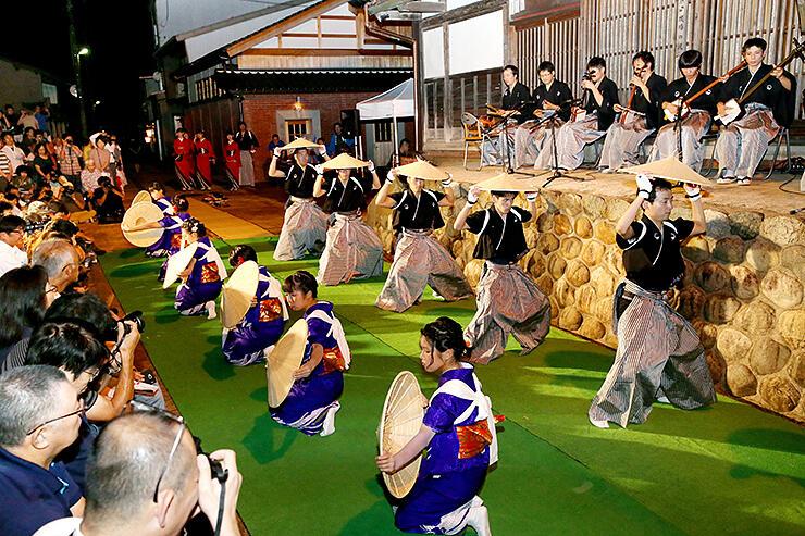 小京都の風情漂う街並みをバックに麦屋節の笠踊りを披露する踊り手=南砺市城端