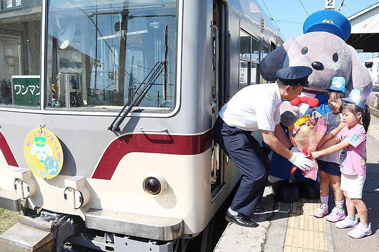 ヘッドマークを冠した電車の前で運転士に花束を渡す園児
