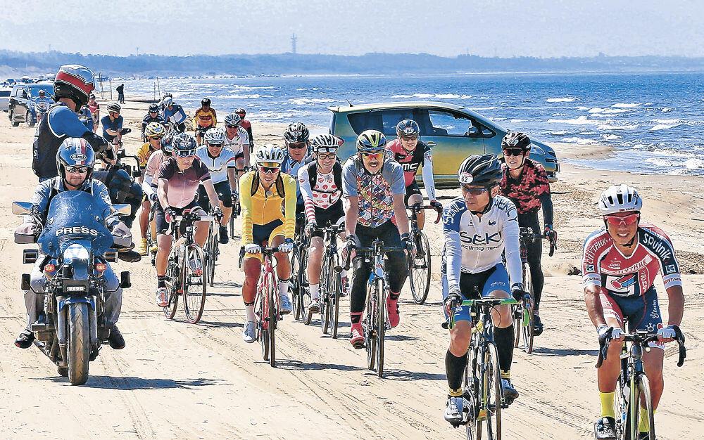 日本海を背に能登路を駆け抜けるサイクリング愛好者=羽咋市の千里浜なぎさドライブウェイ