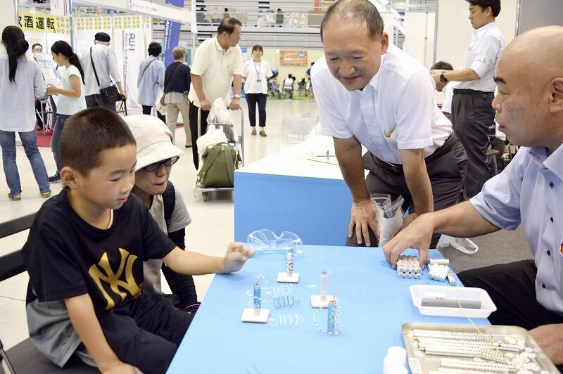導線と磁石、電池でモーター作りを楽しむ親子連れら=9月14日、サンドーム福井