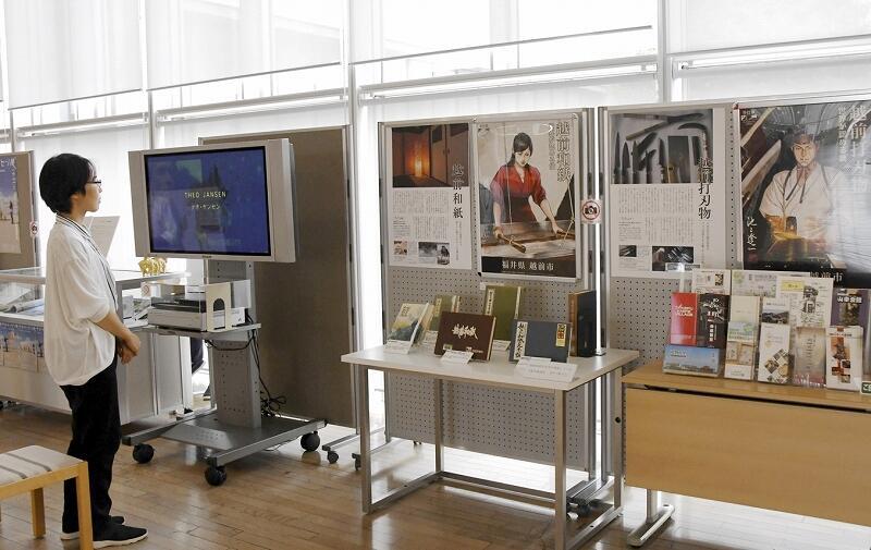 越前和紙の見本帳など伝統工芸に関する図書やポスターが並ぶ企画展=9月13日、福井県福井市の県立図書館