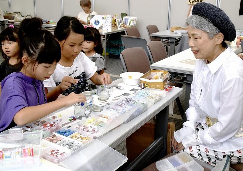 カラフルなガラスを小瓶に貼っていく子どもたち=9月15日、福井新聞社・風の森ギャラリー