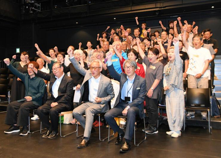 監修を務める西村さん(最前列右から2人目)と共に気勢を上げるシニア劇団のメンバーら