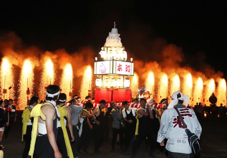 火の粉を散らす「連合大三国」の前で威勢よくみこしを担ぐ住民ら