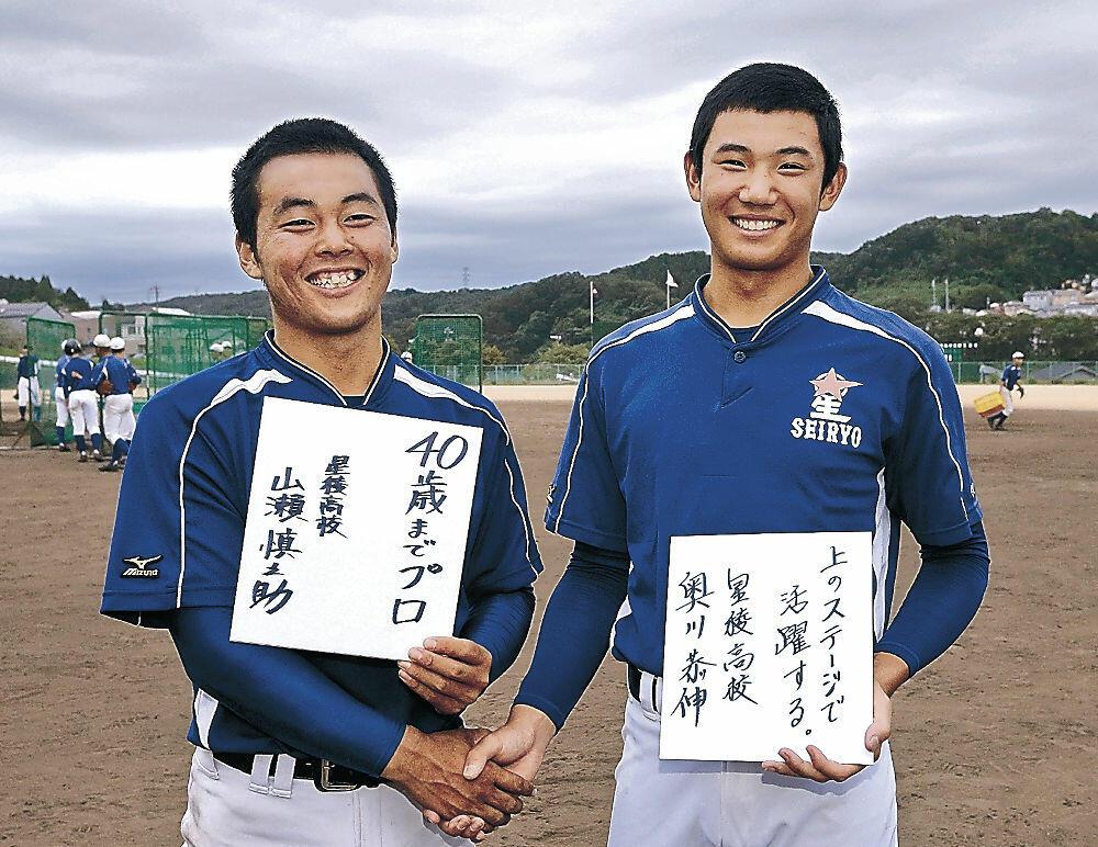 将来の目標を書いた色紙を手に握手する奥川(右)と山瀬=星稜高グラウンド