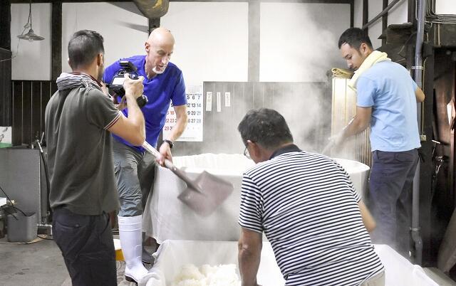 イタリアのテレビ番組制作会社から日本の食の魅力に取材を受けるムニッキさん(左から2人目)=9月19日、福井県美浜町早瀬