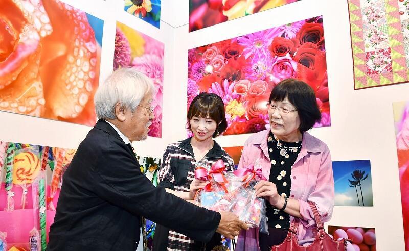 土田ヒロミ館長(左)から記念品を手渡される親子=9月20日、福井県あわら市金津創作の森