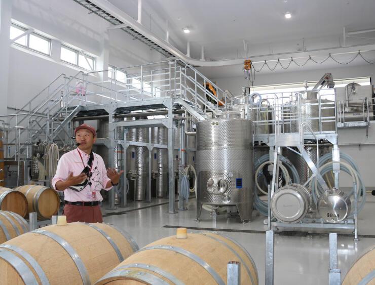 椀子ワイナリーの醸造タンクを紹介する小林弘憲ワイナリー長
