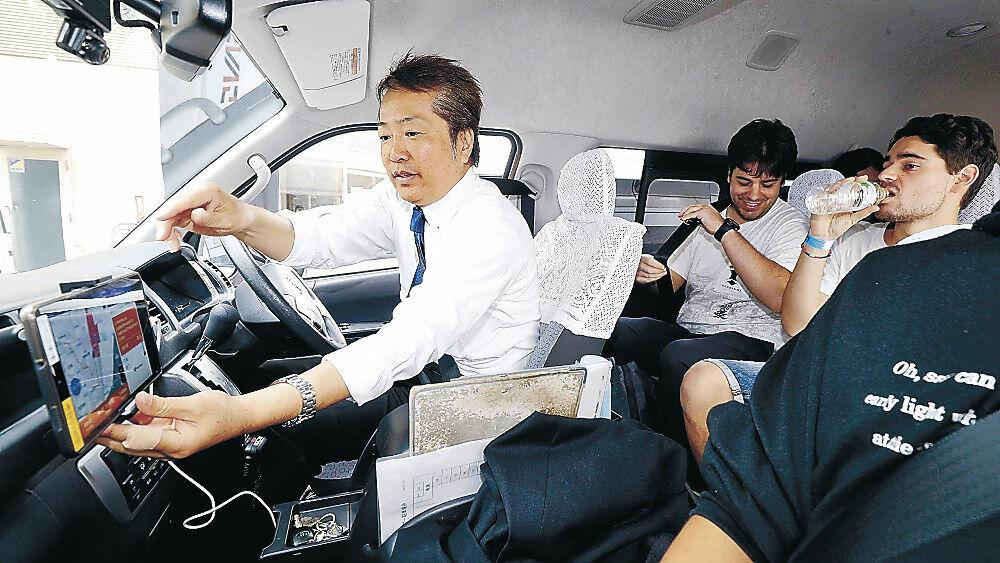 AIによるタクシーの配車システムを利用する外国人観光客=金沢駅前