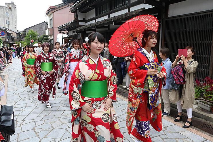華やかな着物姿で石畳通りを練り歩く学生