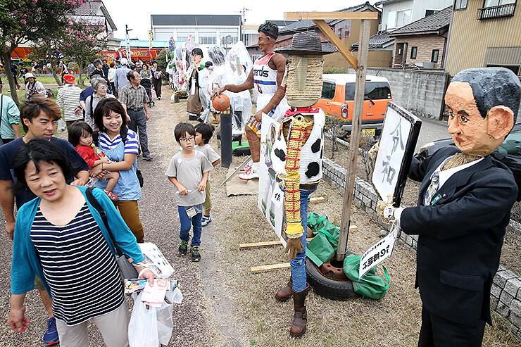 世相を反映したかかしが並ぶ中田かかし祭=中田中央公園