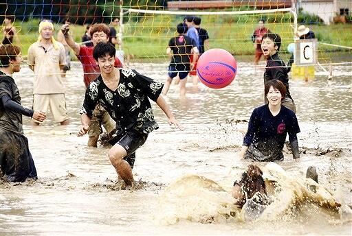 泥まみれになりながら懸命にプレーする選手=22日、福井県越前町大谷の陶寿園水田特設コート