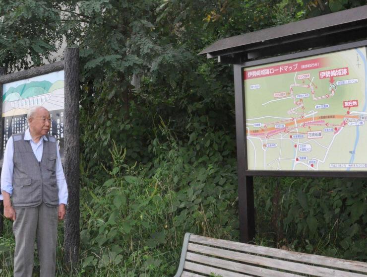 虚空蔵山の麓に設けた看板を眺める佐藤さん。伊勢崎城跡について紹介している