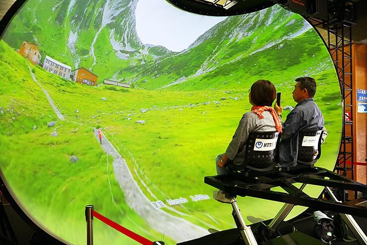 空中にいるような気分で立山の映像を楽しむ観光客