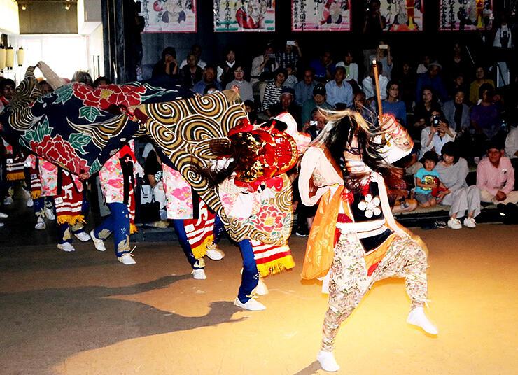 観客の前で勇壮な獅子舞を披露する万尾青年団