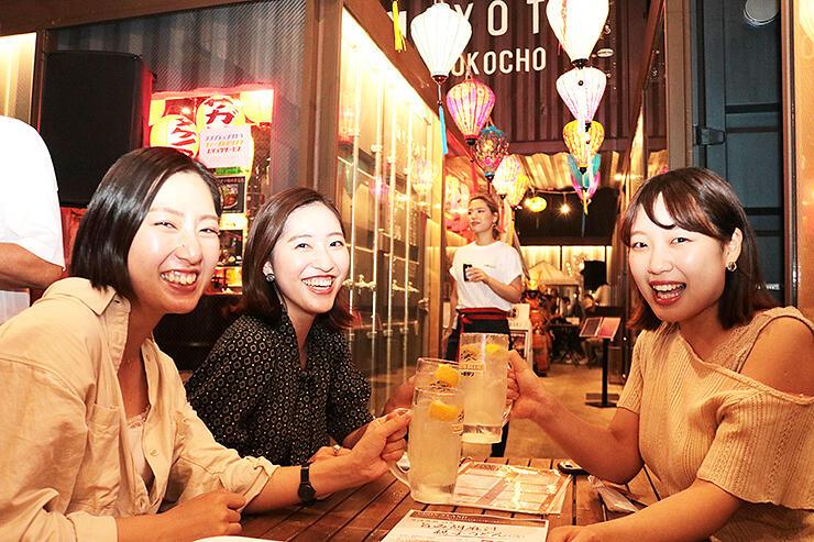 1周年を記念し飾られたランタンの下でお酒を楽しむ女性=富山市総曲輪の「あまよっと横丁」