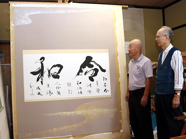 出品作を説明する中村支部長(左)と原相談役