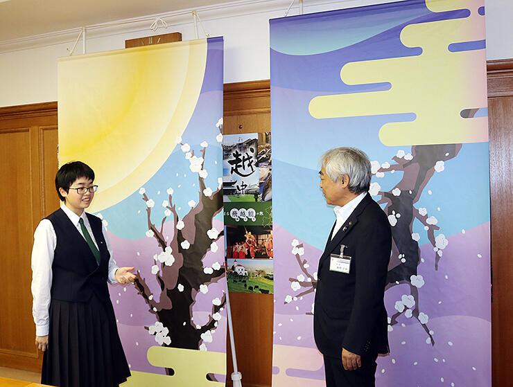 高橋市長に懸垂幕のデザインを説明する高儀さん(左)=高岡市役所