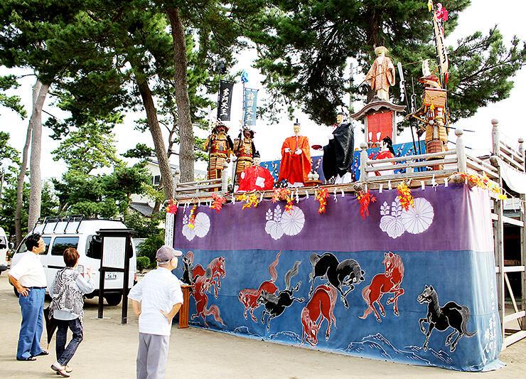 飾人形などが置かれた築山を見上げる参拝客