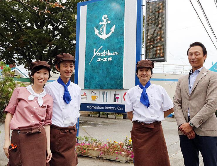新調した看板を背に、新たな店づくりに意欲を見せる(左から)杉川実鈴さん、智之さん、修治さん、小竹社長