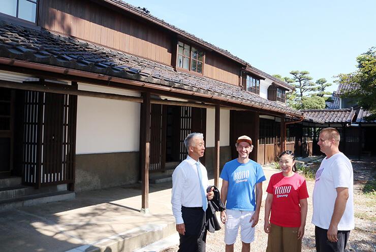 旧米蔵の前で語り合う(左から)桝田社長、プリエソルさん、コティネックさん夫妻=富山市東岩瀬町