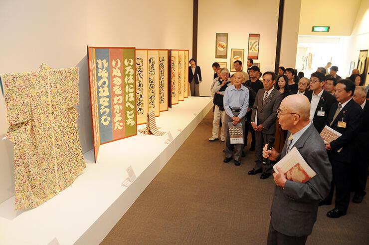 芹沢の代表作が並ぶ会場。収集した宗廣さん(右)による作品解説が行われた
