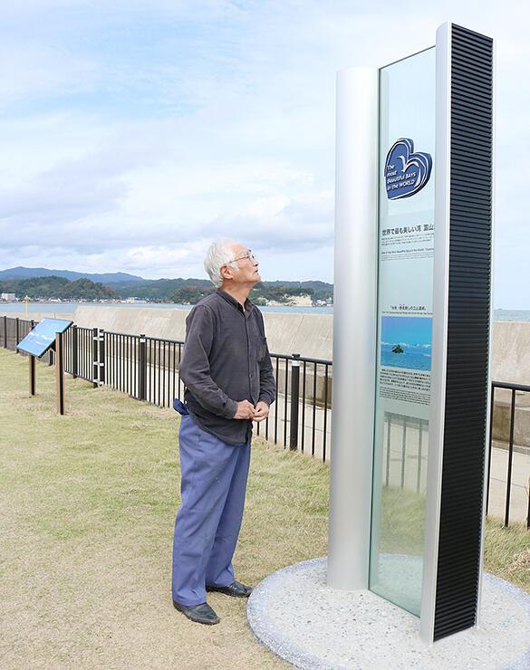 湾クラブ加盟記念のモニュメント。奥にあるのが海越しの立山連峰の案内看板