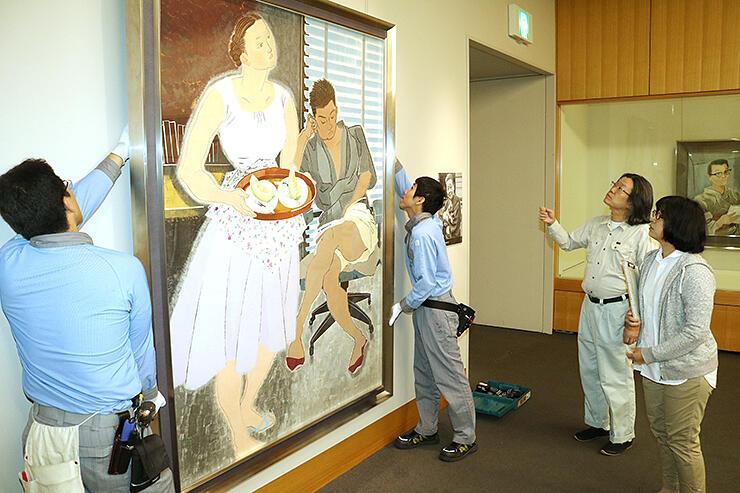 小倉遊亀の「家族達」(左)などを展示していく学芸員ら