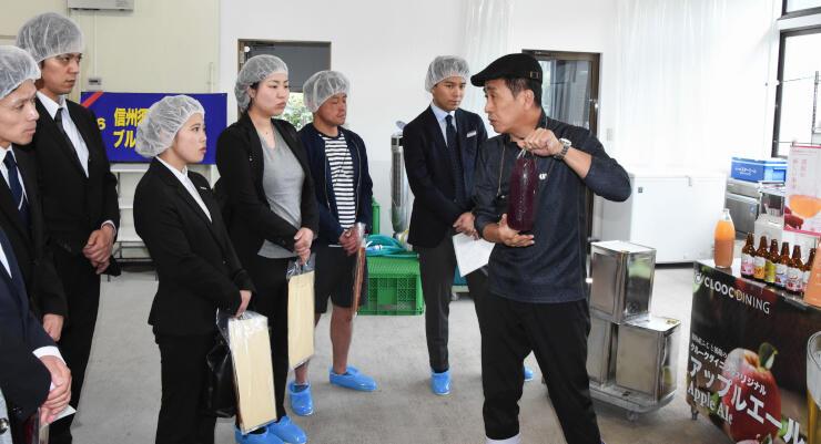 フルーツエールの醸造から保存までの説明を聞くモニターツアー参加者たち