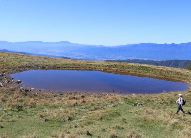 伊那谷を背景に青空の色を映し出した「天空の池」=9日、大鹿村