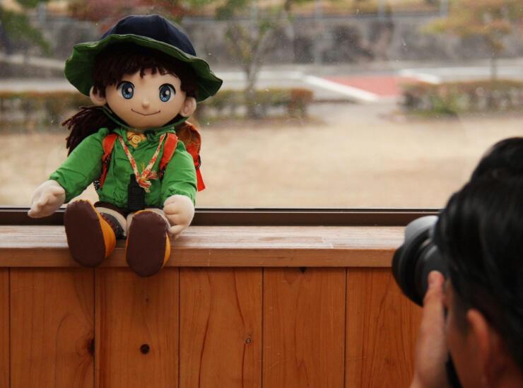 御嶽山火山マイスターネットワークのキャラクターの縫いぐるみにカメラを向ける近藤さん
