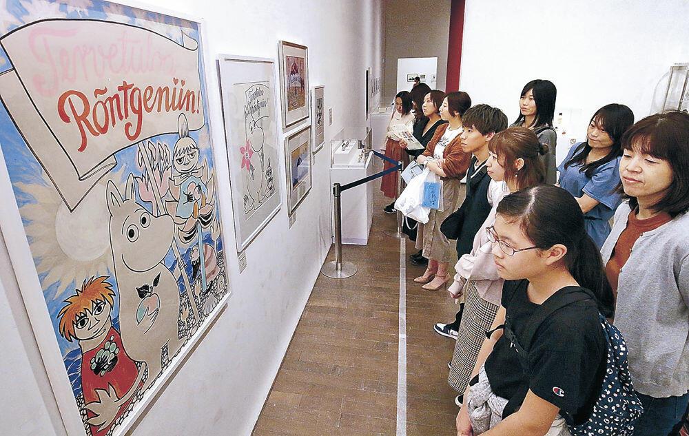 ムーミンシリーズの貴重な作品に見入る来場者=金沢21世紀美術館